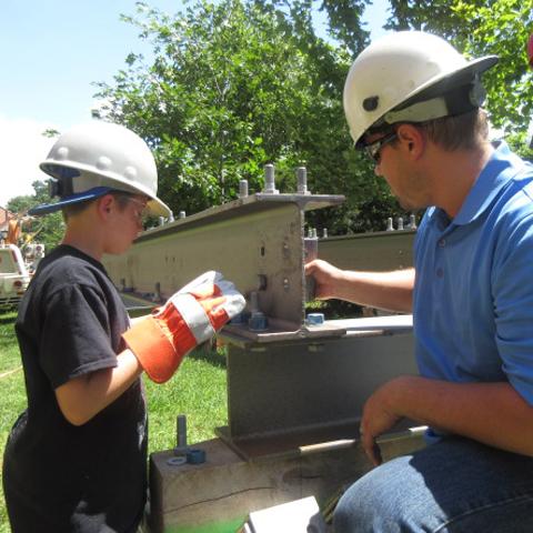 summer camper working with metal beams